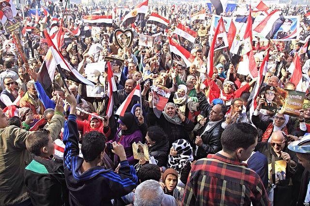"""Sostenitori del nuovo presidente egiziano Abdel Fattah al Sisi festeggiano i risultati delle elezioni a piazza Tahrir, al Cairo, il 29 maggio 2014 - credito foto: """"Pro-government crowds gather in Tahrir Square - Cairo - 25-Jan-2014"""" von Hamada Elrasam for VOA - http://gdb.voanews.com/BDB12AEC-CF19-4A8C-A522-B7C05B884AF0_mw1228_mh548_s.jpg. Lizenziert unter Gemeinfrei über Wikimedia Commons."""