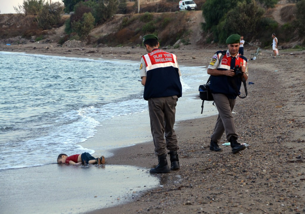RETRANSMISSION TO REMOVE REFERENCE OF BID TO MOVE TO CANADA -Paramilitary police officers investigate the scene before carrying the lifeless body of Aylan Kurdi, 3, after a number of migrants died and a smaller number were reported missing after boats carrying them to the Greek island of Kos capsized, near the Turkish resort of Bodrum early Wednesday, Sept. 2, 2015.  The tides also washed up the bodies of Rehan and Galip on Turkey's Bodrum peninsula Wednesday, Abdullah survived the tragedy. (ANSA/AP Photo/DHA) TURKEY OUT  ONLINE OUT